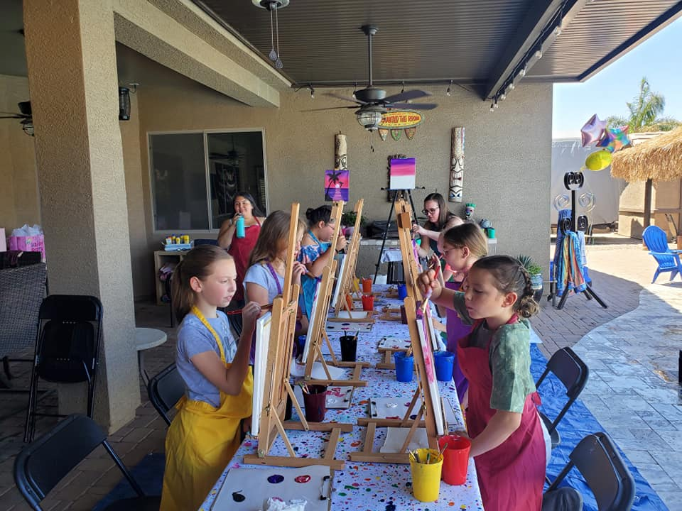 Girls on back patio during a birthday paint party by the pool